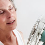 A woman having a hot flash using a fan to cool off.