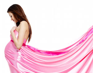 Youn beautiful pregnant woman in rosy dress - white background